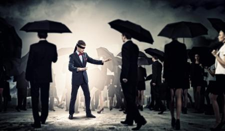ojos vendados: Imagen de hombre de negocios con los ojos vendados en caminando entre un grupo de personas