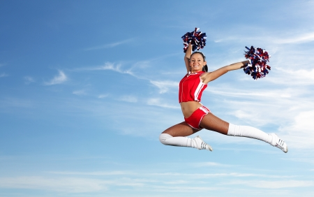 Young beautiful female cheerleader in uniform jumping high Stock Photo - 18745589