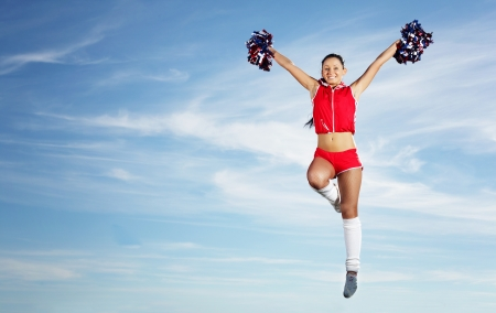 Young beautiful female cheerleader in uniform jumping high Stock Photo - 18745585