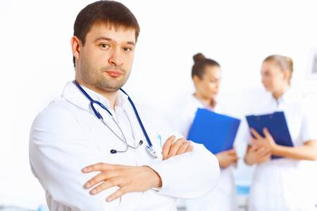 Young male doctor in white uniform with collegues on the background Stock Photo - 18767823