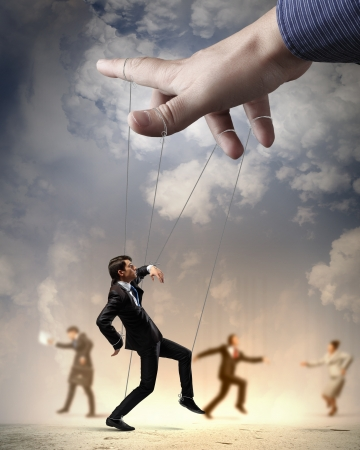 controlled: Businesspeople marionette on ropes controlled by puppeteer