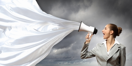 businesswoman in grey suit screaming into megaphone photo