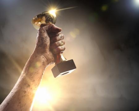 trofeo: Lo hicimos Apriete a mano el ganador de la copa contra el cielo oscuro rel�mpago
