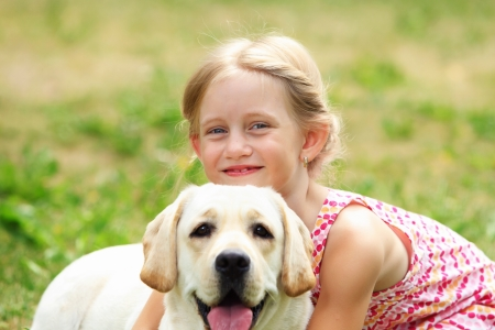 fondle: A little blond girl with her pet dog outdooors in park