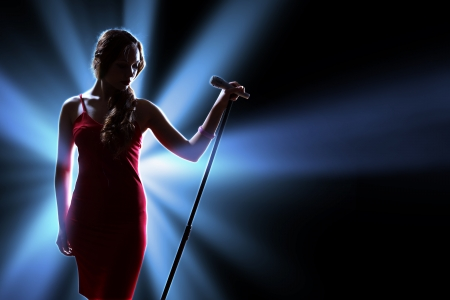 female singer: Female singer on the stage holding a microphone