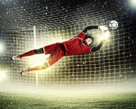 Goalkeeper catches the ball   At the stadium, in the spotlight  photo