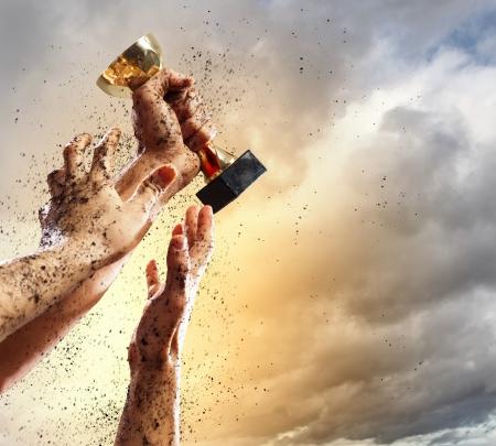 Manos que aprietan el ganador de la copa contra el rayo cielo oscuro