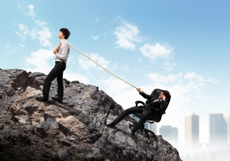 Image of two young businessmen pulling rope atop of mountain against city background photo