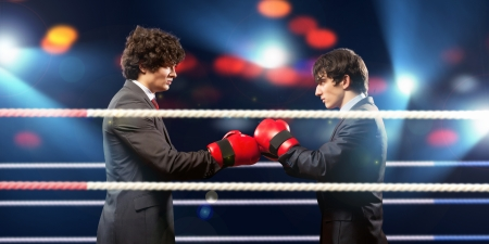 Two young businessman boxing againts dark background conceptual collage
