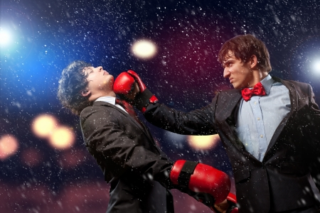Two young businessman boxing againts dark background   conceptual collage Stock Photo - 18892239