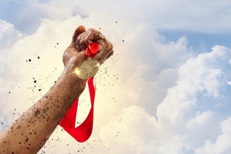 Hand gehouden medaille tegen een stormachtige hemel