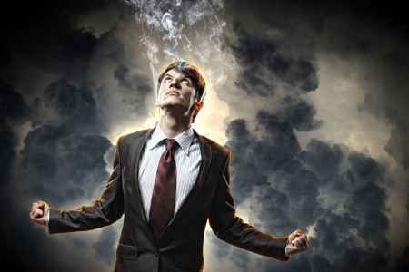 businessman in anger with fists clenched and steam above head photo