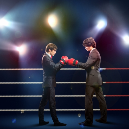 Two young businessman boxing againts dark background   conceptual collage Stock Photo - 18892216