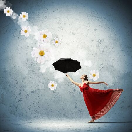ballet dancer in flying satin dress with umbrella and flowers photo