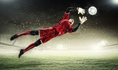 goalkeeper: Goalkeeper catches the ball   At the stadium, in the spotlight