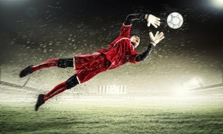 portero futbol: Portero coge el bal�n en el estadio, en el punto de mira