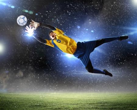 joueurs de foot: Gardien de but attrape le ballon Au stade, sous les projecteurs Banque d'images