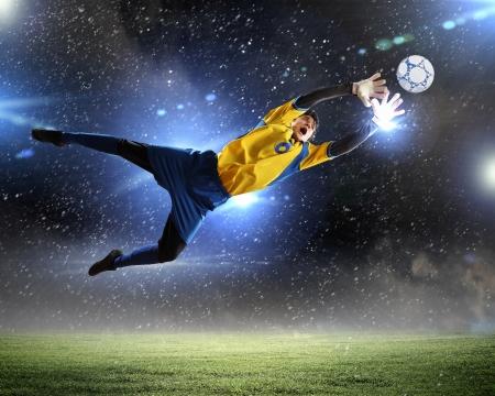 Torwart fängt den Ball im Stadion im Rampenlicht