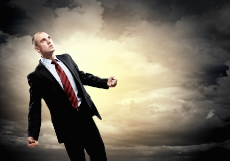 amok: Image of young businessman in anger standing against cloudy background Stock Photo
