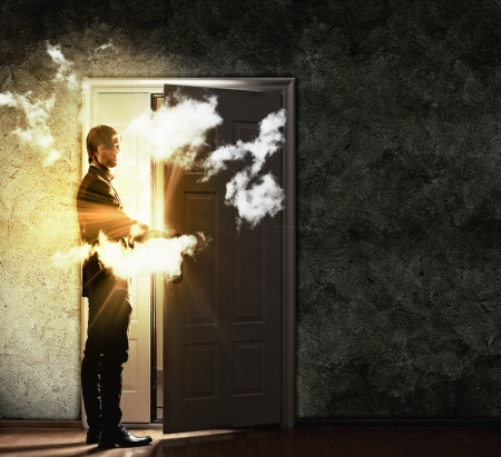 Image of young businessman opening door with lights Stock Photo