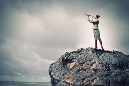 marketresearch: Image of businesswoman looking in telescope standing atop of rock Stock Photo