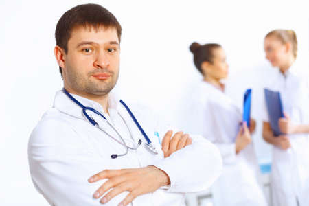 Young male doctor in white uniform with collegues on the background Stock Photo - 19036474