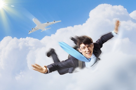 Conceptual image of young businessman flying with parachute on back Stock Photo - 19036726