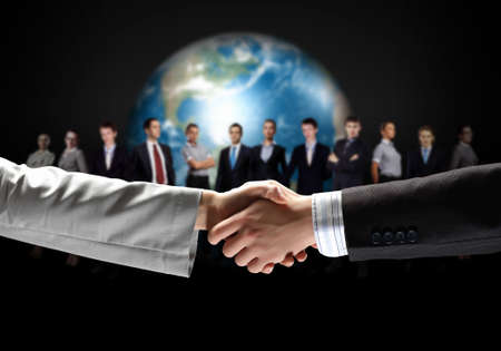 business handshake against black background and standing businesspeople Stock Photo - 19036854