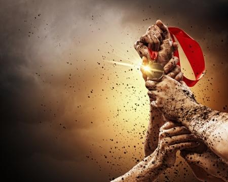 victoire: Mains serrer m�daille dans un ciel orageux sombre Banque d'images