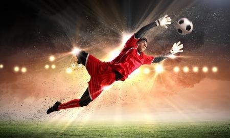 goal keeper: Doelman vangt de bal op het stadion, in de schijnwerpers
