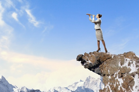 Image of businesswoman looking in telescope standing atop of rock photo