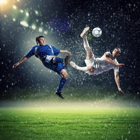 twee voetballers in sprong om de bal te slaan in het stadion onder regen