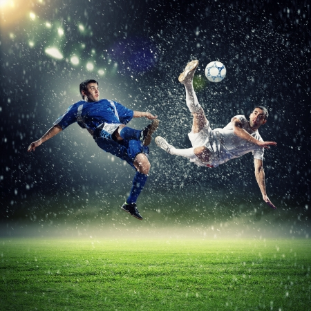 two football players in jump to strike the ball at the stadium under rain Imagens