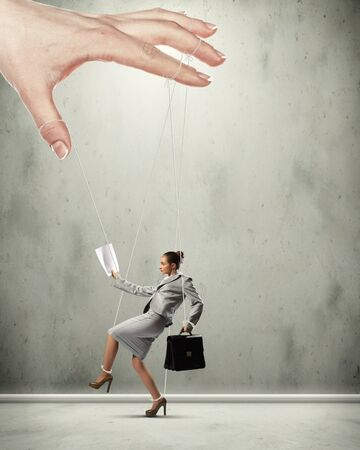 tiedup: Businesswoman marionette on ropes controlled by puppeteer Stock Photo