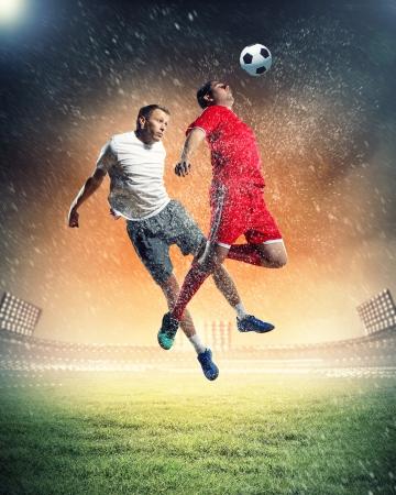 jugadores de futbol: dos jugadores de f�tbol en el salto para golpear la pelota en el estadio
