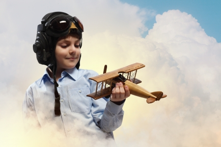 Image of little boy in pilots helmet playing with toy airplane against clouds background photo