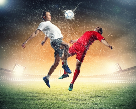 inair: two football players in jump to strike the ball at the stadium