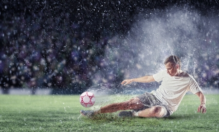 and shoot: football player in white shirt striking the ball at the stadium under the rain Stock Photo