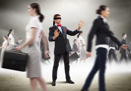 incapacity: Image of businessman in blindfold walking among group of people Stock Photo