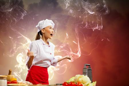 Asian female cook in anger against color background with shine effects photo