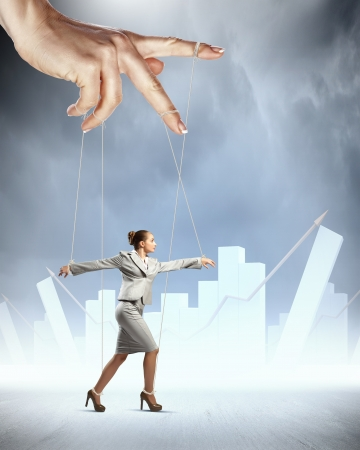 Businesswoman marionette on ropes controlled by puppeteer against bars background photo