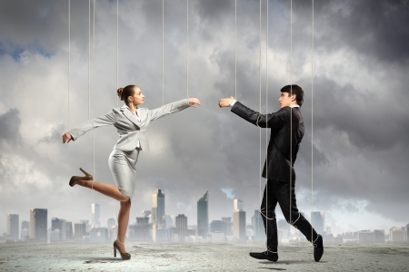 dictator: Image of businesspeople hanging on strings like marionettes against city background  Conceptual photography