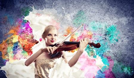 Afbeelding van mooie vrouwelijke violist speelt met tegen kleurrijke achtergrond