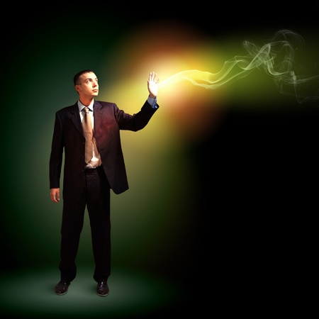 Young successful businessman holding a shining light in his hand as a symbol of success and advancement