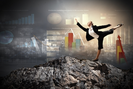 young businesswoman standing on one leg atop of mountain against diagram background Stock Photo - 19305186