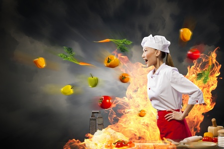 Asian female cook in anger with flyung vegetables against color background with shine effects photo