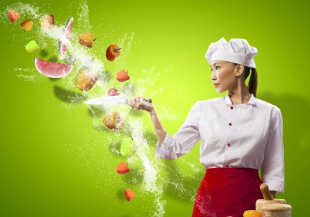 Asian female cook with knife cutting fruits and vegetables in air