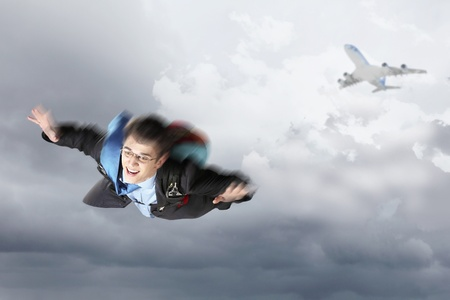 Conceptual image of young businessman flying with parachute on back Stock Photo - 19304784