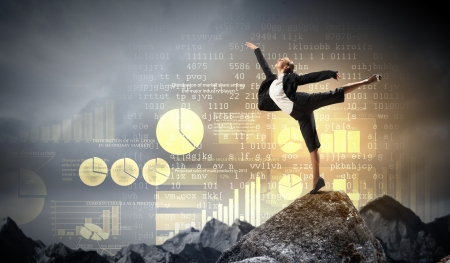 young businesswoman standing on one leg atop of mountain against diagram background photo