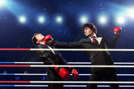 Two young businessman boxing againts dark background   conceptual collage photo